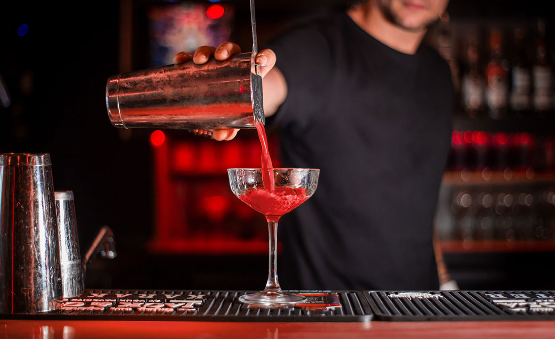 Bartender pouring drink into martini glass